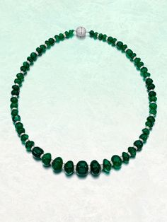 Emerald and diamond necklace. Designed as a graduated row of polished emerald beads, this necklace is accented with brilliant-cut diamond spacers. | Sotheby's
