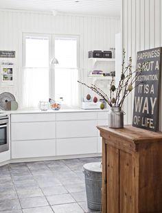 Eteisestä on avoin kulku keittiöön. Pieni seinäkaappi on ostettu porvoolaisesta sisustuskaupasta ja avohyllyt Ikeasta. Tiinalla on vanhassa Porvoossa kaksi suosikkikauppaa: Våga ja Sisustus Liina Interiör. Eteisen kaapin Tiina hankki huutokaupasta ruokapöydän kanssa. Sisustustaulu on Oliverin kirpputorilta Keravalta. Keittiön ja eteisen kookas lattialaatta on Kaakelikeskuksesta.