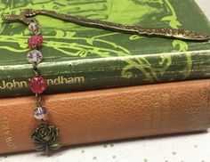 This antique gold coloured bookmark has a floral and hummingbird decoration. A rose shaped charm hangs below pretty pink beads. All metal components are lea. Beaded Bookmarks, Organza Gift Bags, Hummingbird, Antique Gold, Pretty In Pink, Beads, Antiques, Rose, Metal