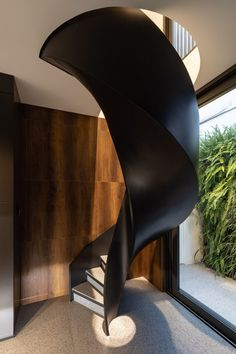 The bedrooms are linked to the main living area by a black kitchen, which features a seating area at one end and a spiralling, black staircase at the other that leads to the first floor.