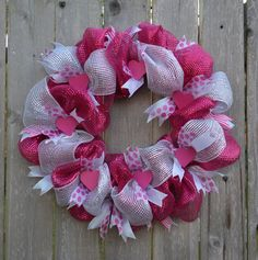 This pretty mesh wreath is about 22 in diameter. Wooden hearts with pins glued on the backs have been added to the wreath and can be moved or
