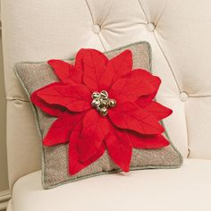"""Give your holidays a little jingle! Polyester pillow with felt petals and metal bells.  dForecorative use only. Imported. 12"""" square."""