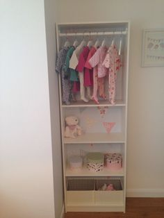 Open closet made from an ikea gersby bookcase. Bunting wallpaper pasted onto the back. For little girls nursery