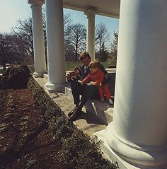 John F. Kennedy plays with his son Jack outside the White House: