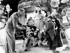 Rare behind the scenes still showing filmmaker Victor Fleming on the set of The Wizard of Oz directing a Munchkinland sequence with Judy Garland.