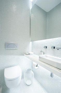 piccolo bagno di servizio rivestito da mosaico di tasselli bianchi esagonali