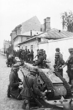 """German soldiers with a """"Goliath"""". The Goliath tracked mine was a remote controlled German-engineered demolition vehicle, also known as the beetle tank to Allies. Employed by the Wehrmacht during World War II this caterpillar-tracked vehicle carried 75–100 kilograms (170–220 lb) of high explosives and was intended to be used for multiple purposes, such as destroying tanks, disrupting dense infantry formations, and demolition of buildings and bridges. Warsaw uprising. 1944. WWII"""