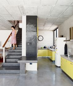 Offset by a shade of canary yellow, the concrete floors in the kitchen of this home in a suburb of Johannesburg, South Africa, tie in with the home's facade, which is also concrete. Photo by Elsa Young.