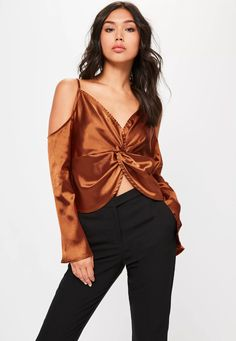 Be a bohemian dream in this blouse - featuring a knot detail at the front, 70s flare sleeves, a cold shoulder style and a bronze hue.