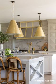 Double islands in the kitchen provide the chef with lot's of food prep space. And the customized design of the kitchen cabinets uniquely add dimension to this neutral color palette. See more photographs of this kitchen: https://alicelanehome.com/portfolio/french-moderne-manor/ | French Moderne Manor designed by Alice Lane