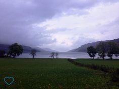 Foto do Lago Ness em um dia nublado. Árvores em volta e gramado.