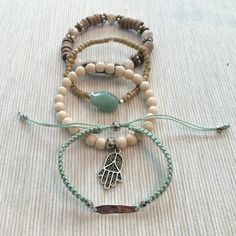 """Set of 4 stacking bracelets! *SOLD LOCALLY* All handmade by me. Adjustable macrame mint green with silver charm, white wood with hanging hamsa charm, tan wood with stone and mixed wood with howlite stone. Perfect for spring and stacking with watch! All made with love and hope you enjoy. Other than the macrame they are made with a stretchy cord at 7"""" so will fit most wrists! Jewelry"""