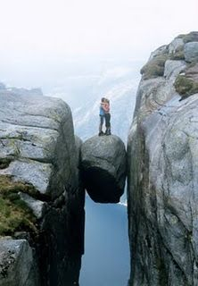 Kjeragbolten- in Norway where this boulder is wedged. Would love to see it, the thought of standing on it makes me vomit a little.