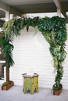A tropical ceremony arch with palm leaves and wild greenery | Brides.com