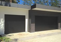The modern architecture of this house is finely complimented by this custom , flush, aluminum garage door.  The dark aluminum is sturdy and gives off a contemporary feel. All of our doors at Ziegler Garage Doors Inc. are designed and made in house. #modernhomes #garage #garagedoors #modern #paloalto #contemporary #remodel #house #renovate