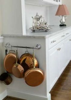 """<p>Don't let the side of your cabinet go to waste: Install a short rail to magically turn the empty space into storage. Since the bar probably won't hold your entire collection, opt to hang the items you use most often — or the prettiest ones (like these copper beauties).</p><p><a href=""""http://the2seasons.com/2012/10/30/why-i-chose-carrera-marble-countertops/"""">See more at The 2 Seasons »</a></p>"""