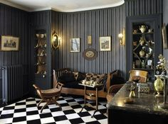 /\ /\ . Maurice Ravel . La petite maison à Montfort l'Amaury . Full of daring, black and white checkered carpeting contrasts with classical gray striped walls in the living room. Ravel designed a rounded recess for the early 19th century Louis XVI sofa.