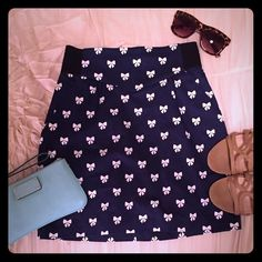 Bow Skirt  How cute is this skirt! Navy blue with white bows, exposed zipper in back, & pockets in front. Waist measures 12 in. wide (sides are elastic so it stretches!), length is 16.5 in. 98% cotton, 2% elastic. In great condition. H&M Skirts