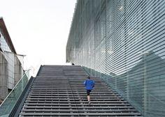 A layer of glass louvres wraps this Paris sports centre.