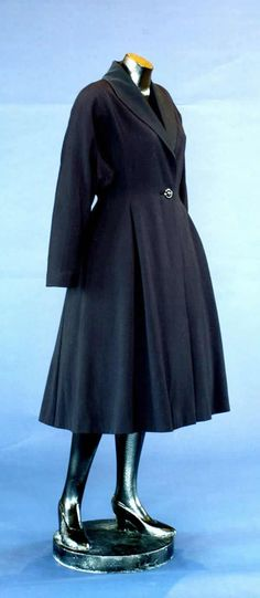 "Coat, Marshall & Snelgrove: ca. 1951, English, ribbed wool with collar, lapels of silk grosgrain. ""The cut of the coat has all the features of the 'New Look', the softly rounded shoulder line with 'Magyar sleeves' and the very full skirt."""
