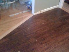Natural color hardwood transition to dark brown hand scraped distressed hardwood floor