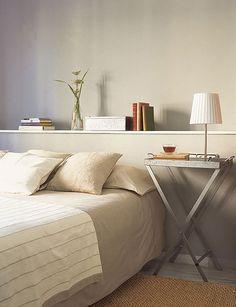 Cabecero de obra, pintado del mismo color que la pared con una repisa. Las mesitas son muy chulas, y la alfombra de coco le da un toque.