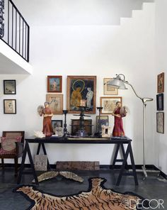 A Worldy Apartment In India - ELLE DECOR The sitting room's hand-embroidered rug is by Lesage Intérieurs, the votive dolls are early 20th century, and the gilt-wood wings on the floor are Baroque; Lesage bought the lamp 20 years ago from a surgery-tool shop and found the 1920s fresco fragments on the street.