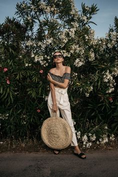 What to wear on a summer holiday in Span gingham crop top with Moroccan round straw bag and white high waisted trousers with golden hoop earrings