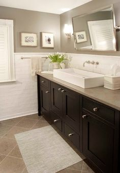 A new first floor Powder room for a restored 100 year old Farmhouse in northern New Jersey. The vessel sink over the stained wood vanity and wall mounted faucet are notable details, offering a modern take on a traditional home interior.