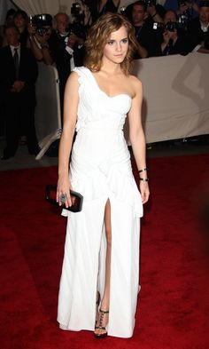 """Emma Watson One Shoulder Dress"" -   Emma walked the red carpet in a pristine white, one-shouldered couture gown with a center slit and ruffled embellishments. She looked fresh and polished.  Brand: Burberry"