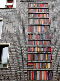 Wall of Books. A 10m-high wall in Amsterdam West, designed with ceramic books.