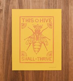 """Dress up your walls with this hand-carved queen bee art print. Reading, """"This hive shall thrive,"""" in blocky type, each one has been letterpress printed from an original woodcut design. Hang it high to celebrate all of the bees in your hive."""