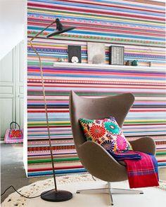 Het bonte fotobehang vanauthentieke lintjes, kantjes en bandjes uit oma's naaidoos vormt een net zo vrolijke als folklorische achtergrond voor de klassieke Egg Chair van Arne Jacobcen.