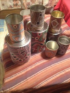 Tin cans covered with aboriginal paper and contact. If you are using the tin cans with children you need to ensure there are no sharp edges that can be dangerous. A good tip is to use an old fashioned can opener to run around the edge of the can to make it smooth and safe for handling. These cans are practical and great for promoting culture and sustainability.