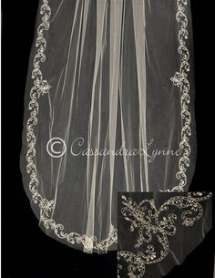 This bridal veil is exquisite! The slightly scalloped edged is designed in silver embroidery that is accented with sequins, bugle beads and rhinestones. It is 108 inches long by 72 inches wide, on a f