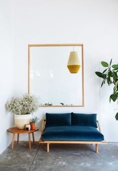 blue velvet love seat and warm neutral accents create a welcoming and modern…