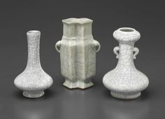 A GROUP OF CRACKLE-GLAZED VASES  19TH/20TH CENTURY Two vases covered in a white glaze suffused with dark grey 'iron wire' crackle, the other of double lozenge (fangsheng) shape and covered in a pale bluish-grey glaze suffused with dark grey 'iron wire' and faint gold 'golden thread' crackle. Tallest 5½ in