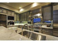 Gourmet kitchen with smoky maple cabinetry, antique mirror back splash & quartzite slab counter tops - 200 Congress Ave, 41q, The Austonian,  Austin TX #kitchens #austinrealestate #homedecor