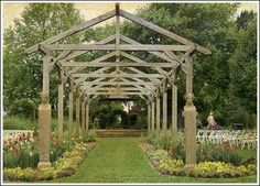 Why not make a open air/pergola for an outdoor wedding/  Still be as pretty even without the carved stone bases.  Add natural materials at the base, sunflowers? branches with leaves?  tufted grasses?