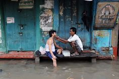 BUSINESS AS USUAL: A barber shaved a customer at his temporary shop alongside a flooded street in Kolkata Sunday. Heavy rains have disrupted normal life as several parts of the city became waterlogged and train service was partially disrupted. (Dibyangshu Sarkar/Agence France-Presse/Getty Images)