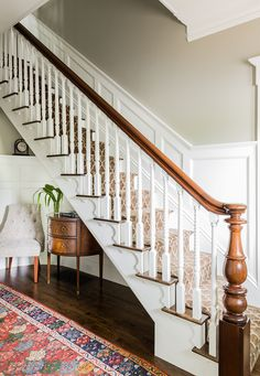 Simple stick-style staircase balusters on the staircase were replaced with alternating vertical and spiral fluted balusters inspired by the roped corner boards on the home's exterior. Scrolled skirt boards were added to the stairs, modeled after the Italianate brackets on home's exterior. The stair treads and flooring were replaced with reclaimed antique oak. The handrail and newel posts were re-used. High wainscot paneling add formality and character.