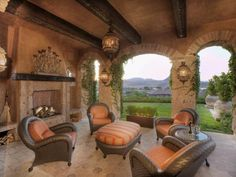 This opulent patio space from designer Thomas Oppelt has arching entrances lined with bricks, exposed wood beams and outdoor brick fireplace. An ornate candle-holder forms a visual focal point on the fireplace mantel, and a seating area is highlighted by ornate light fixtures, comfortable outdoor chairs, ottoman and glass side table.