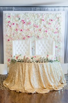 sweetheart table with gold sparkle tablecloth and flower background