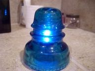 Old glass insulator over LED tealight 'candle'.