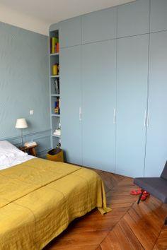 Le bleu ciel des murs met en valeur le jaune moutarde dans cette chambre