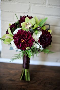 This is a very sophisticated bouquet. Love the pairing of garden flowers, like these burgundy zinnias, with the lime green orchids with the black satin wrapped stems.