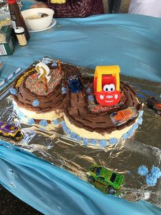 I made my 2 year old Grandson this racing car cake. It was made with 2 round butter cakes, I cut one 3cm side off one (I ate that) the same off the other one, joined the flat sides together then added the cut off piece to create a bridge. 1/2 the butter cream icing went on the sides and then added cocoa to the other 1/2 to the top and across the bridge. Bullets were used for the road sides and tubes of edible icing made it easy to decorate. The decorating icing came from Woolworths.