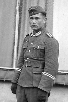 Ostlegion soldier. Given the man's Asiatic facial features he probably belongs to the Turkistan Legion. His Osttruppen collar tabs and shoulder boards show that he holds the rank of Zugführer (Oberfeldwebel). However the two aluminium braid rings worn on both sleeves just above the cuffs indicate that in addition to his substantive rank he is also a 'Khaupt-Fel'dfebel' (Hauptfeldwebel), i.e. a company sergeant-major, which was an appointment not a rank. German Uniforms, War Dogs, The Third Reich, Army Uniform, German Army, Military History, World War Two, Armed Forces, Wwii