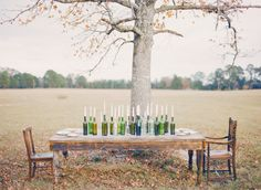 simple centerpiece lineup of wine bottles holding taper candles Photography and Styling by Three Nails Photography http://www.threenailsphotography.com