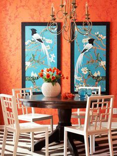 Vivid Color Scheme: Orange + Blue Vibrant and theatrical, this dining room?s color scheme is anything but shy and quiet. A mix of modern and traditional furnishings keeps the look chic yet family-friendly. Complementary blue tones in the large pair of framed prints keeps the orange walls from getting too warm. High-contrast black and white in the table, chairs, and rug lift the palette to an even higher level of sophistication.
